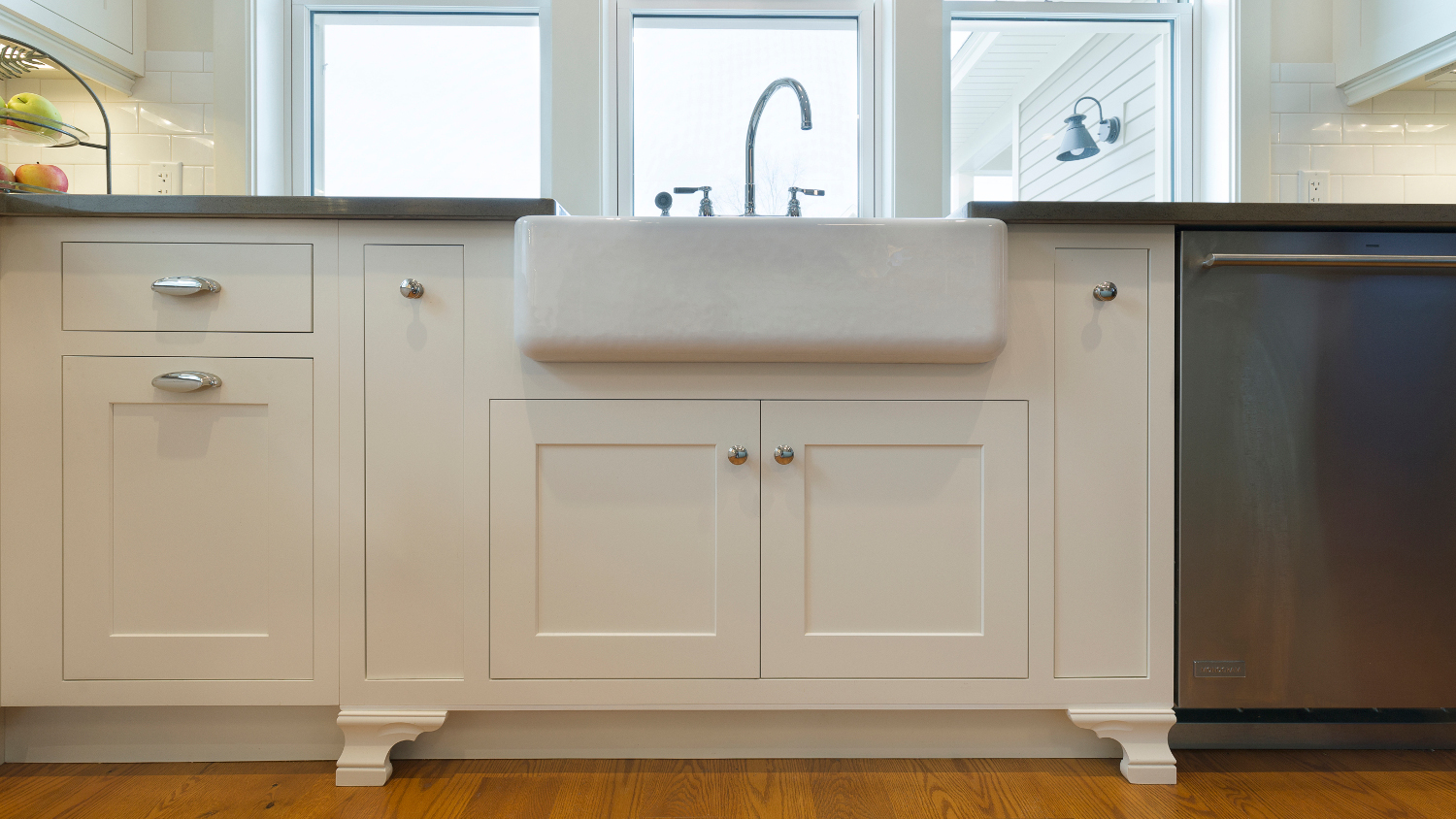 The farm style apron front sink base has handy pullouts that house necessary cleaning aids. The ogee feet create the charm of a furniture piece.