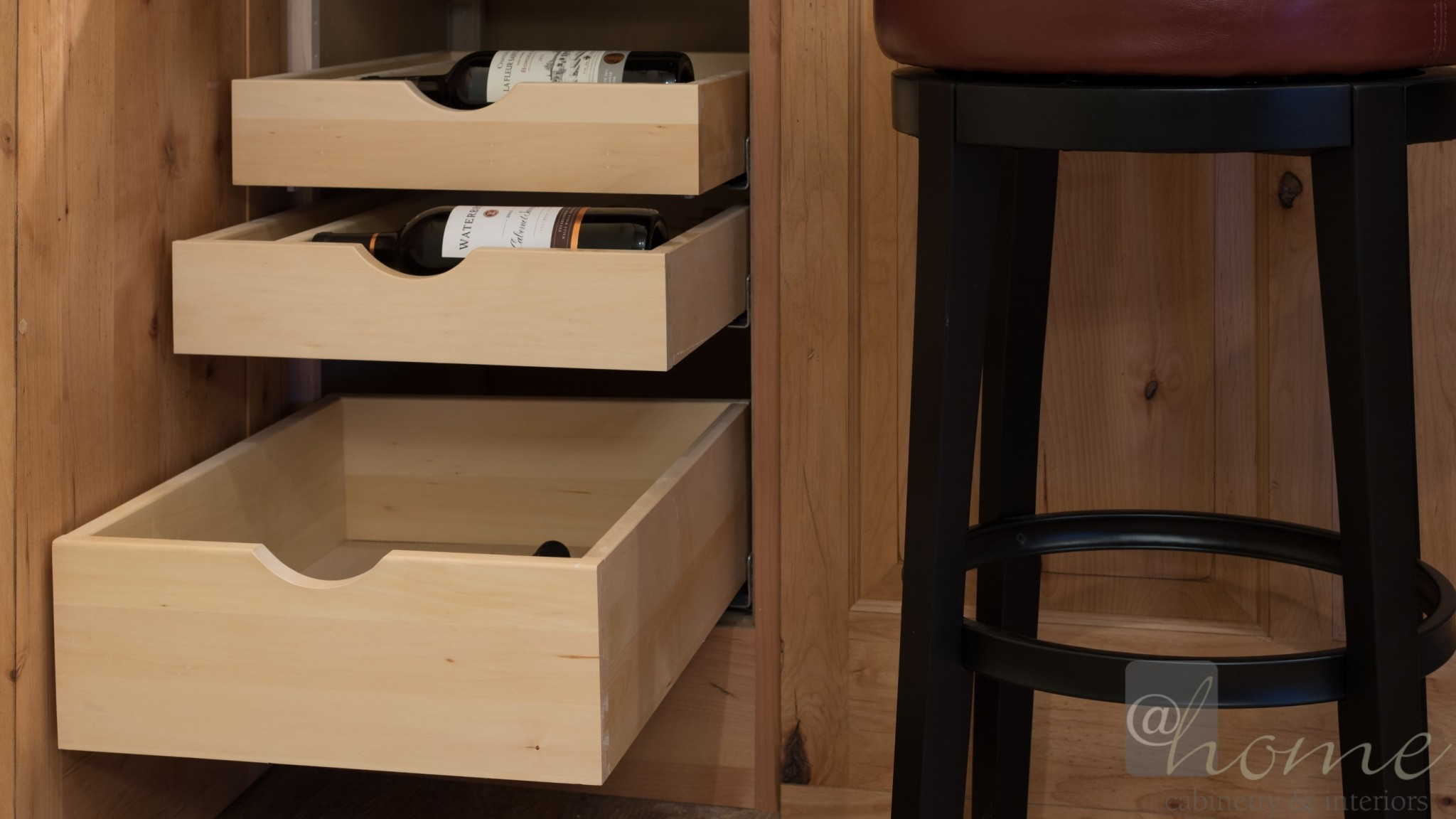 Hidden discreetly in the bar wainscot paneling: a touch latch door that reveals rollout wine storage drawers!